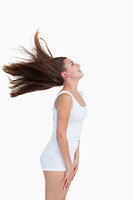 Side view of a young woman standing while flipping her hair