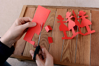 Cutting a chain of red paper dolls with scissors