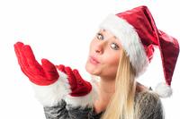 M?dchen mit Weihnachtsm?tze pustet ?ber ihre H?nde